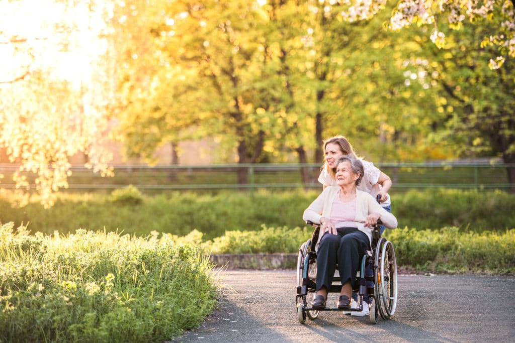Senior in wheelchair with caregiver outside