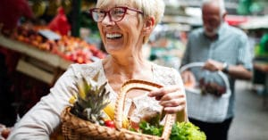 Senior woman with basket of fruit in the market