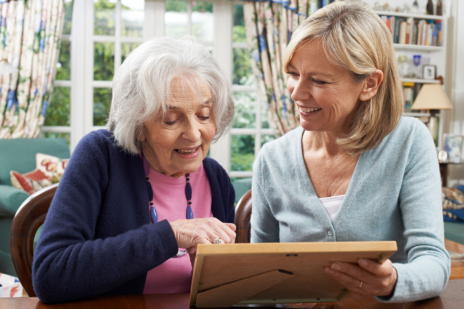 Senior woman and daughter looking at photo together