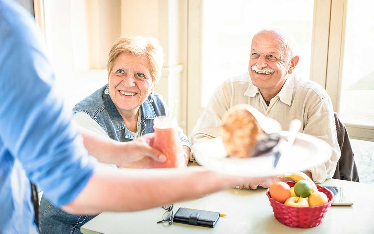 Seniors dining with fruit and bread